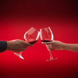 Couple holding glasses of red wine toasting Stock Photo