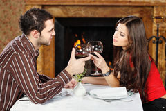 Couple holding glasses of wine and cheers Stock Images