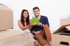 Couple Holding Green House Model At New Home Royalty Free Stock Image