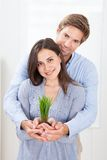 Couple holding green sprout at home Stock Image