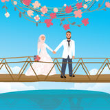 Couple holding hand in bridge woman wearing scarf veil Islamic symbol Royalty Free Stock Photo