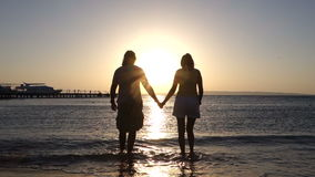 Couple holding hand at ocean sunset stock footage
