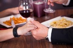 Couple holding hand at restaurant Royalty Free Stock Image