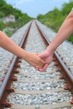 A couple holding hand together on the train track. Focusing on holding hand together with blur bokeh train track and tree background Stock Photography