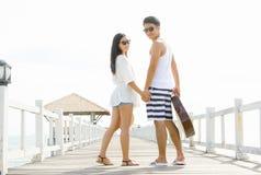 couple holding hand while walk along bridge pier Royalty Free Stock Photography