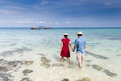 Couple holding hand walking in to crystal clear sea with long ta. Il boat background, Krabi, Thailand Stock Photography