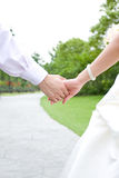 Couple holding hands in the park. Wedding feelings. Couple holding hand in hand Royalty Free Stock Photography