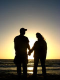 Couple Holding Hands. A silhouette of a man and a woman, holding hands on a beach in Australia against a sunset Stock Photos
