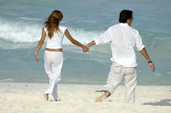 Couple holding hands. Young attractive couple walking along the beach holding hands royalty free stock photos