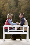 Couple holding hands. On a bench at a lake in autumn royalty free stock images