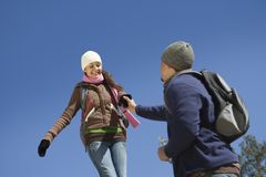 Couple Holding Hands Against Blue Sky Stock Photo