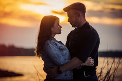 Couple holding hands during an amazing sunset. Stock Photos