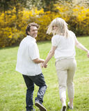 Couple holding hands with back to camera running through park Stock Images