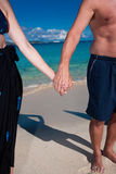 Couple holding hands on a beach Stock Photos
