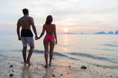 Couple Holding Hands On Beach At Sunset Back Rear View, Young Tourist Man And Woman On Sea Holiday Stock Images