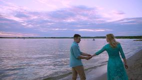 Couple holding hands on beach sunset on honeymoon vacation travel. Happy romantic young lovers, man and woman walking on. Beautiful beach stock video