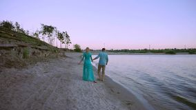 Couple holding hands on beach sunset on honeymoon vacation travel. Happy romantic young lovers, man and woman walking on stock video footage