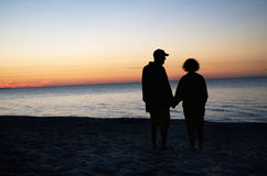 Couple Holding Hands On Beach At Sunset Stock Images