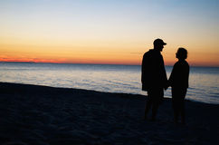 Couple Holding Hands On Beach At Sunset. Male and female holding hands and looking out onto a body of water at sunset on a beach Stock Photo