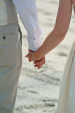 Couple holding hands during a beach wedding ceremony Stock Photo