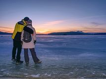 Couple holding by hands. Beautiful people in puffy jackets stock photography