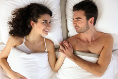 Couple holding hands in bed Stock Image