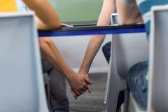Couple holding hands below desk in classroom Stock Image