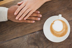 Couple holding hands beside cappuccino Royalty Free Stock Image