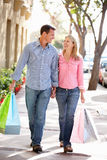 Couple holding hands carrying shopping Stock Photos