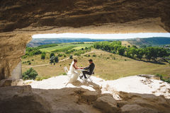 Couple Holding Hands in Cave. Couple holding hands sitting at table in cave Stock Images