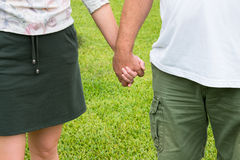 Couple Holding Hands. Close up of couple holding hands with green grass background stock photo