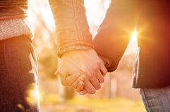 Couple holding hands. Closeup of loving couple holding hands while walking at sunset Royalty Free Stock Photos