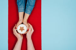 Couple holding hands with coffee on colorful table, top view Royalty Free Stock Images