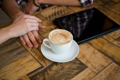 Couple holding hands with coffee cup and tablet PC on table in cafe Stock Photos