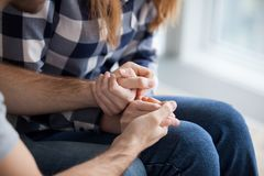 Couple holding hands, showing love and empathy close up. Couple holding hands, consoling, showing love and empathy close up. Husband support, understanding, care stock photography
