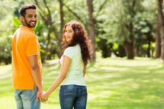 Couple holding hands. Cute indian couple holding hands and looking back outdoors Stock Photos