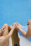 Couple holding hands and dipping feet in swimming pool Royalty Free Stock Photos