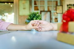 A couple holding hands each other in restaurant with a golden gi. Ft box with red ribbon Royalty Free Stock Photography