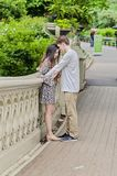 Couple hugging in Central Park in New York City. Couple holding hands face to face on Bow Bridge in Central park in New York City royalty free stock images
