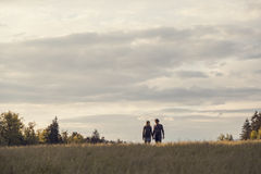 Couple holding hands in field below cloudy sky Stock Images