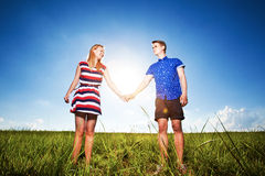 Couple holding hands on green field Royalty Free Stock Images