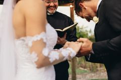 Traditional wedding ceremony rituals. Couple holding hands with groom acknowledging the consent before the priest. Close up of bride and groom during outdoor Stock Photos