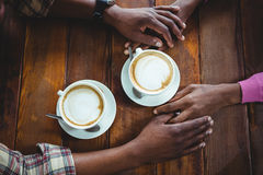 Couple holding hands while having coffee Royalty Free Stock Photography