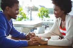 Couple holding hands while having coffee Stock Image
