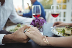 Couple holding hands while having meal Stock Images