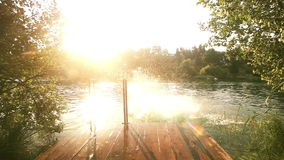 Couple holding hands and jumping into water from river dock stock footage