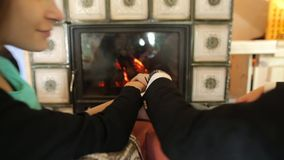A couple holding hands and kissing near the fireplace