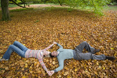 Couple holding hands and laying in autumn leaves Royalty Free Stock Photo