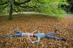 Couple holding hands and laying in autumn leaves Royalty Free Stock Images