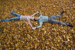 Couple holding hands and laying in autumn leaves Royalty Free Stock Photography